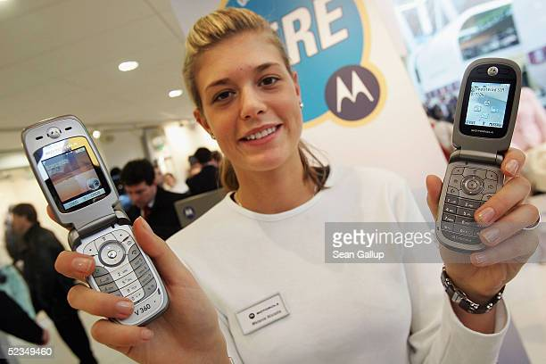 A hostess displays the V360 and V235 mobile phones from Motorola both of which have the PPT function or Push To Talk which allows the phones to be...