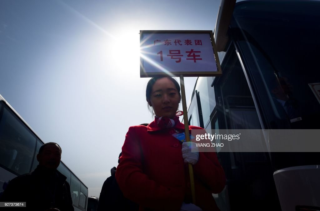 TOPSHOT - A hostess from a hotel holds a guide board for delegates next to a shuttle bus outside the Great Hall of the People after the opening session of the National People's Congress, China's legislature, at the Great Hall of the People in Beijing on March 5, 2018. China's rubber-stamp parliament opens a major annual session set to expand President Xi Jinping's considerable power and clear him a path towards lifelong rule. / AFP PHOTO / WANG Zhao