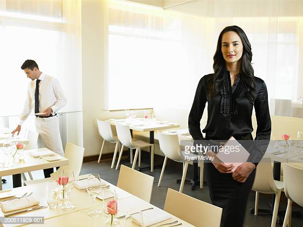 Hostess holding menu in restaurant, waiter setting table in background