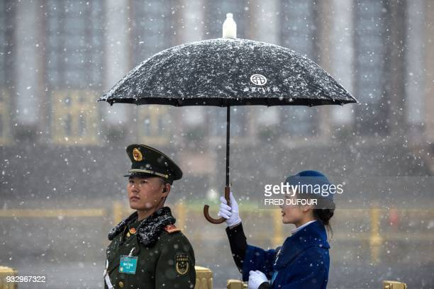 Hostess holds an umbrella for a paramilitary police for a picture at the Great Hall of the People, where China's President Xi Jinping was elected for...