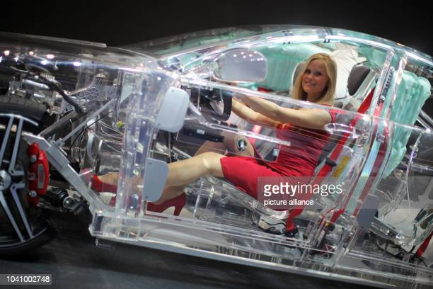 Hostess Lina sits in an acrylic model car in the booth of Thompson Ramo Wooldridge a car safety producer during the press day of the Frankfurt Motor...
