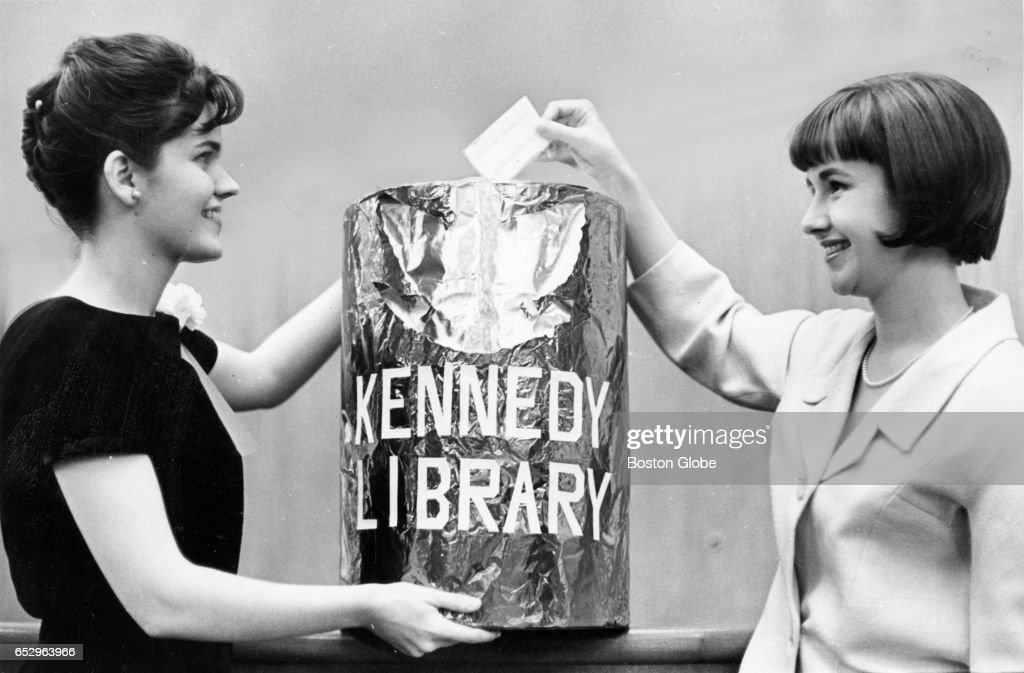 Hostess Linda Scott, left, and Mrs. Rhyne Simpson add donation envelopes to a collection during a fundraising event for the Kennedy Memorial Library in Boston on Apr. 15, 1964.