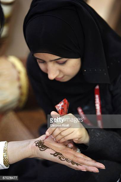 A hostess paints the hand of an attendee with a henna design on the opening day of the Internationale Tourismus Boerse fair on March 08 2006 in...