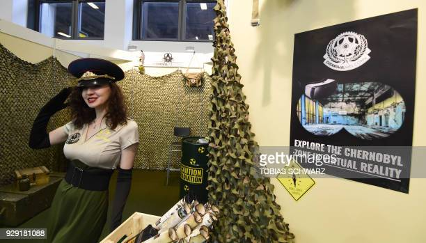 A hostess poses at a booth promoting VR pictures of Chernobyl at the International Tourism Trade Fair in Berlin on March 8 2018 The business platform...