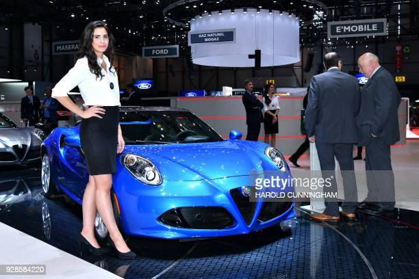A hostess poses next to the new Alpha Romeo 4C Spider Italia at the Italian car maker's booth during a press day ahead of the Geneva International...