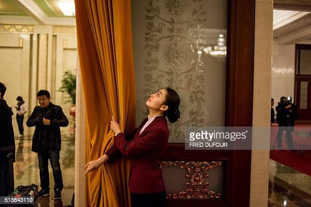 A hostess pulls open a curtain in the Great Hall of the People during the opening ceremony of the National People's Congress in Beijing on March 5...