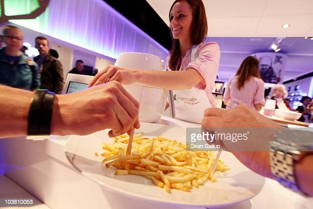 A hostess serves up french fries prepared in the Philips AirFryer which uses no cooking oil at the Philips stand at the 2010 IFA technology and...