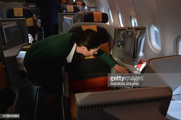A hostess shows a business class seat in an aircraft airbus A330200 fom Italy's airline giant Alitalia during a press conference to present the new...
