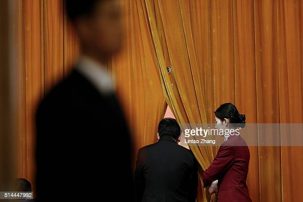 A hostess stands by the curtain at the entrance of meeting hall as the security personnel guarding during the 2nd plenary session of the National...