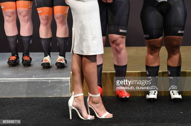 A hostess stands in front of medallists on the podium as they are presented with their medals after the women's team sprint final race at The UCI...
