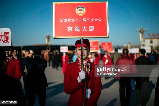 CORRECTION A hostess stands with a board to help delegates find their way at the end of the Chinese People's Political Consultative Conference...