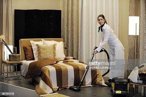 A hostess uses a vacuum cleaner to clean and prepare a stand at the 'Home Textiles' trade fair in the central German city of Frankfurt am Main on...
