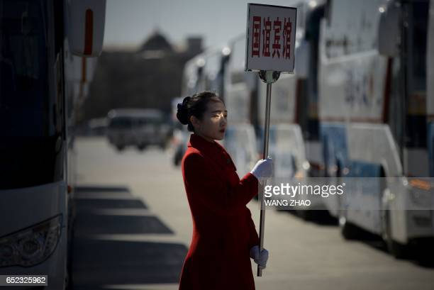 A hostess waits for delegates after the third plenary session of the National People's Congress at the Great Hall of the People in Beijing on March...
