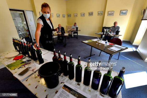 A hostess with a mask serve wine to wine brokers in la Maison du Vin in Margaux on June 4 2020 during a 'primeurs' Bordeaux wines tasting according...