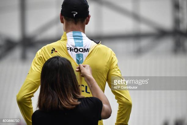 TOPSHOT A hostess zips up the overall leader yellow jersey on Great Britain's Christopher Froome celebrating on the podium at the end of a 225 km...