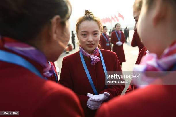 Hostesses discuss on Tiananmen Square after the seventh plenary session of the 13th National People's Congress at the Great Hall of the People on...