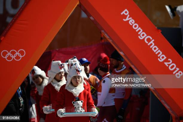 TOPSHOT Hostesses hold mascots during the victory ceremony at the end of the men's downhill at the Jeongseon Alpine Center during the Pyeongchang...