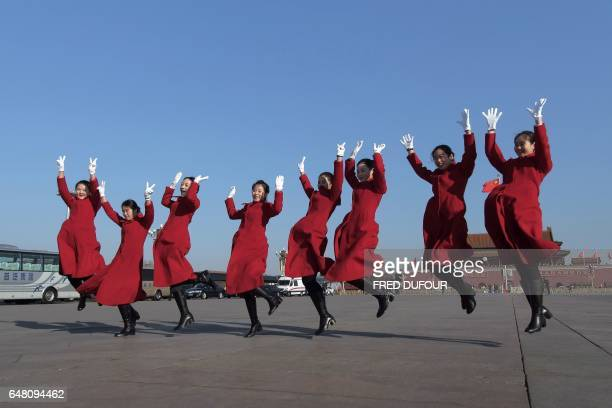 TOPSHOT Hostesses jump as they pose for a picture during the opening of the National People's Congress in Beijing on March 5 2017 China's rubberstamp...