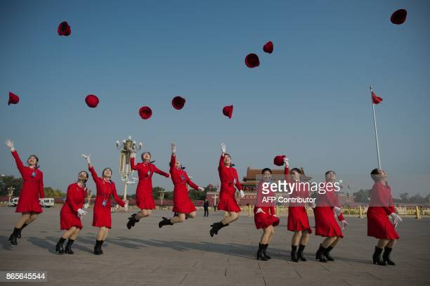 TOPSHOT Hostesses jump in the air and throw their hat on Tiananmen square during the closing session of the 19th Communist Party Congress in Beijing...
