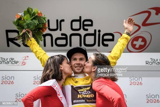 Hostesses kiss overall race winner, Slovenia's Primoz Roglic of Lotto NL-Jumbo team as he celebrates during the final podium ceremony of the Tour de...