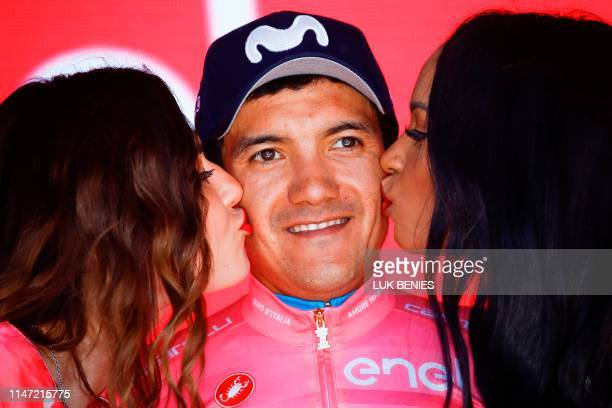 Hostesses kiss Team Movistar rider Ecuador's Richard Carapaz wearing the overall leader's pink jersey as he celebrates on the podium after stage...