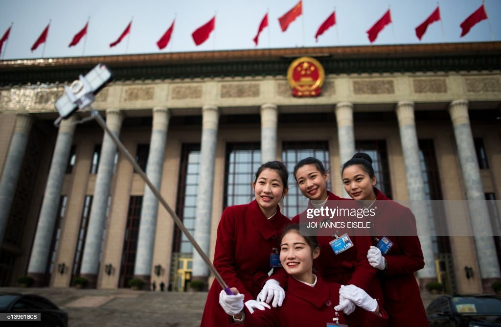 TOPSHOT - Hostesses pose for selfies outside the Great Hall of the People in Beijing during the second day of the National People's Congress on March 6, 2016. China?s Communist-controlled parliament opened its annual session on March 5 and is expected to approve a new five-year plan to tackle slowing growth in the world?s second-largest economy.7 /