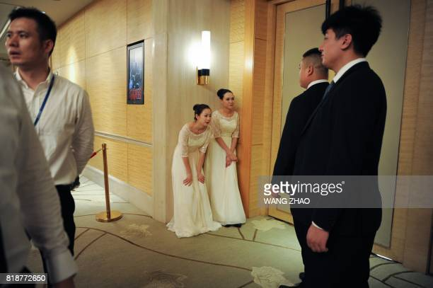 Hostesses stand outside a room where chairman of China's Wanda Group Wang Jianlin, chairman of Sunac China Holdings Limited Sun Hongbin, and chairman...