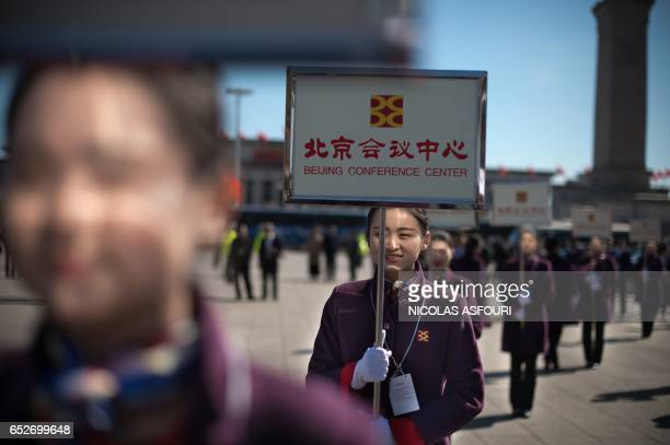 TOPSHOT Hostesses stand with boards to guide delegates to their respective buses after the closing session of the Chinese People's Political...