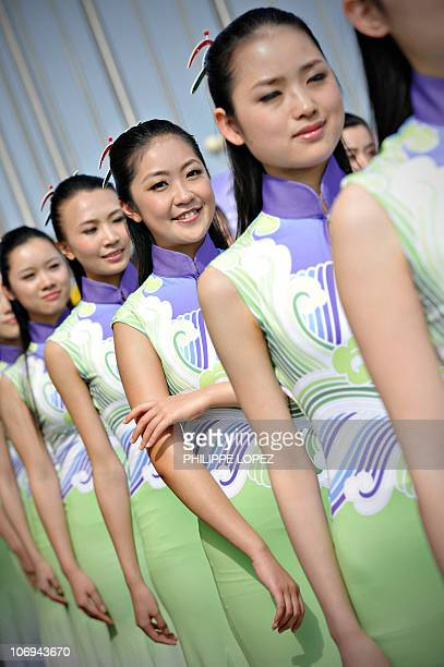 Hostesses wait for the start of the medal ceremony of the women's 1000m dragon boat straight race at the 16th Asian Games in Guangzhou on November...