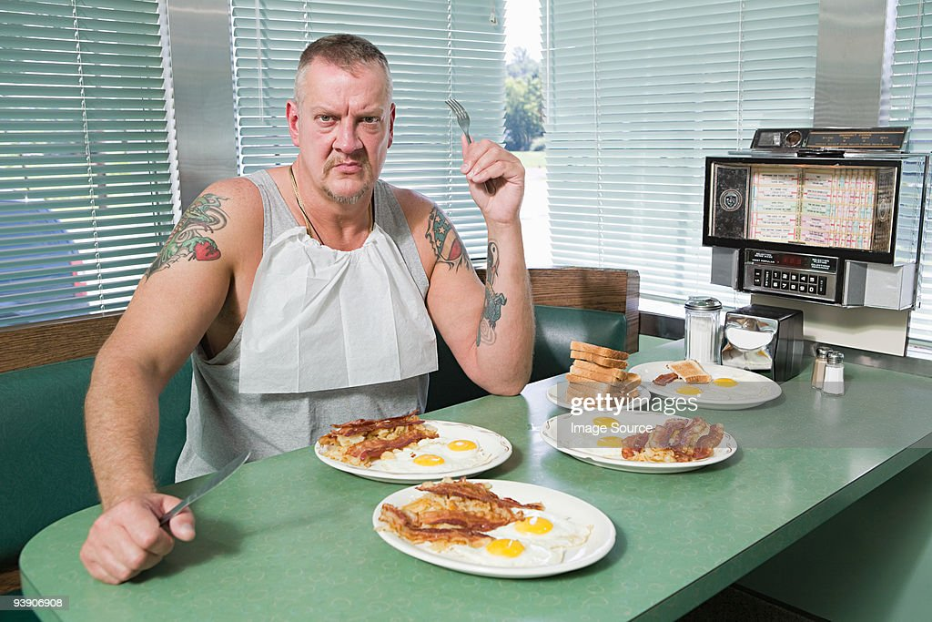 Hostile man with plates of fried food : Stock Photo