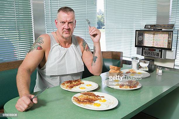 Hostile man with plates of fried food