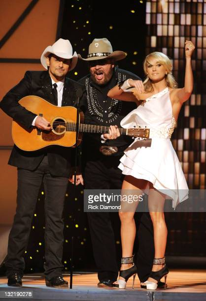 Hosts Brad Paisley and Carrie Underwood speak with Hank Williams Jr. At the 45th annual CMA Awards at the Bridgestone Arena on November 9, 2011 in...