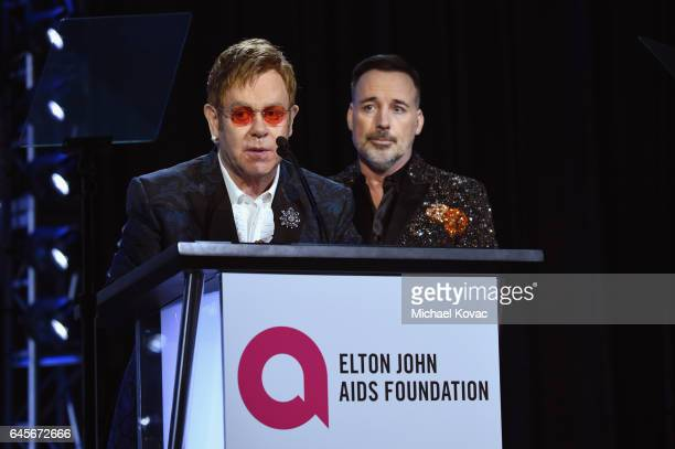 Hosts Elton John and David Furnish speak onstage at the 25th Annual Elton John AIDS Foundation's Academy Awards Viewing Party at The City of West...
