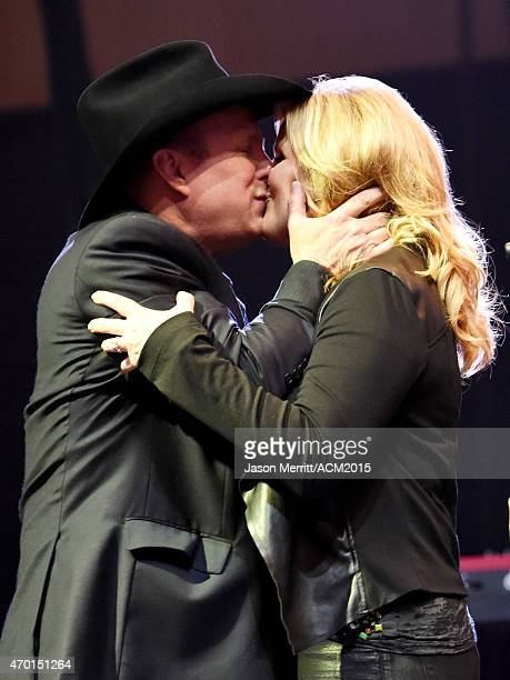 Hosts Garth Brooks and Trisha Yearwood kiss onstage during the ACM Lifting Lives Gala at the Omni Hotel on April 17 2015 in Dallas Texas