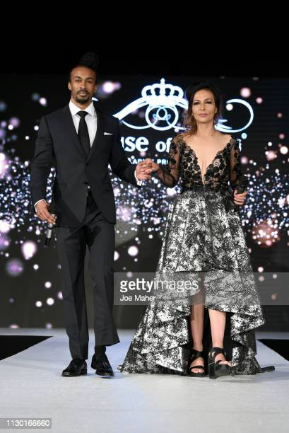 Hosts Tiger Brown and Savita Kaye walk the runway at the House of iKons show during London Fashion Week February 2019 at the Millennium Gloucester...