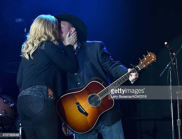 Hosts Trisha Yearwood and Garth Brooks kiss while performing onstage during the ACM Lifting Lives Gala at the Omni Hotel on April 17 2015 in Dallas...