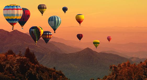 Hot air balloon above high mountain at sunset 1001927840