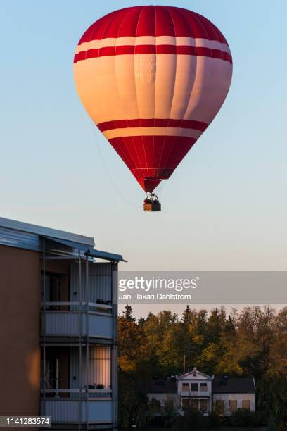 hot air balloon above houses - balloon stock pictures, royalty-free photos & images