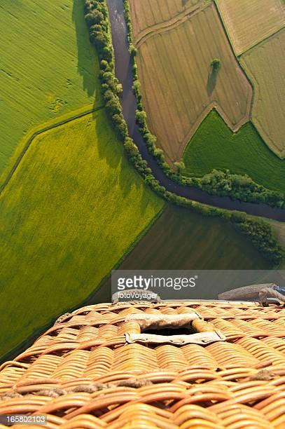 Cesta de globos de aire caliente volando sobre verde paisaje de verano
