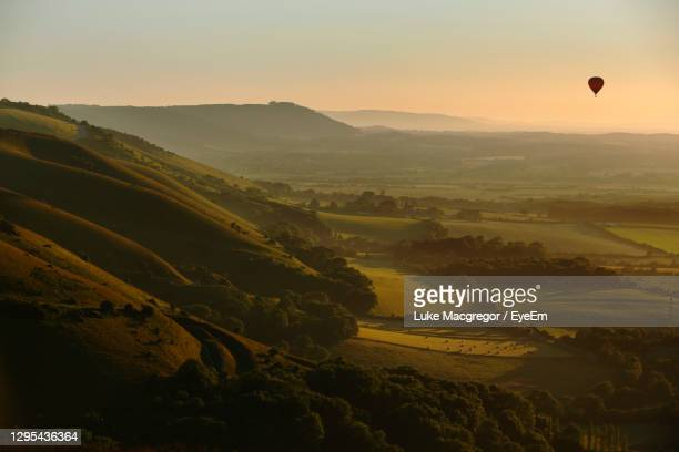 hot air balloon flies at sunset over devil's dyke in the south downs near brighton east sussex, uk - sunrise dawn stock pictures, royalty-free photos & images