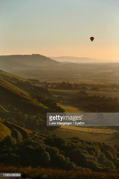 hot air balloon flies at sunset over devil's dyke in the south downs, near brighton, east sussex, uk - sunrise dawn stock pictures, royalty-free photos & images