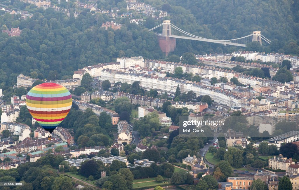 A hot air balloon flies over the Clifton Suspension bridge as they take to the skies as they participate in the mass assent at sunrise on the second day of the Bristol International Balloon Fiesta on August 11, 2017 in Bristol, England. More than 130 balloons have gathered for the four day event, now in its 39th year and now one of Europe's largest annual hot air balloon events, being hosted in the city that is seen by many as the home of modern ballooning.