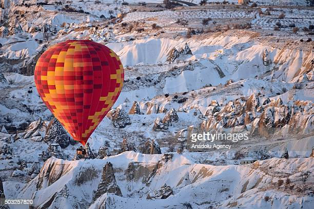 Hot air balloon flies over the famous volcanic rock formations during the winter season in Cappadocia a historical region in central Anatolia in...