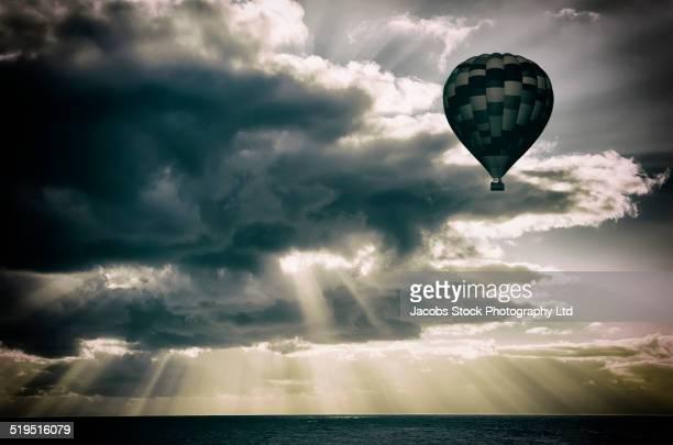Hot air balloon floating in sunbeams