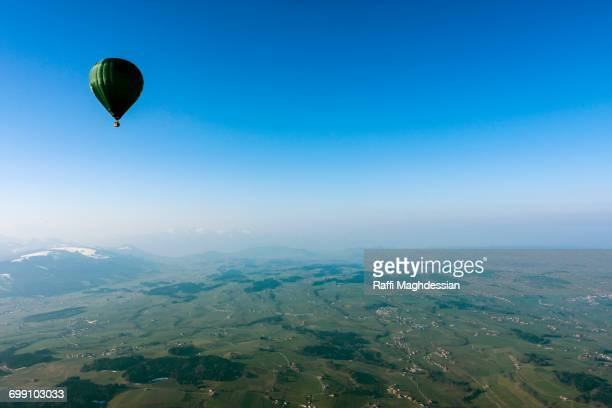 A Hot Air Balloon Floating Through The Blue Sky In Switzerland