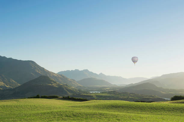 Hot Air Balloon Flying Above Rolling Landscape Wall Art