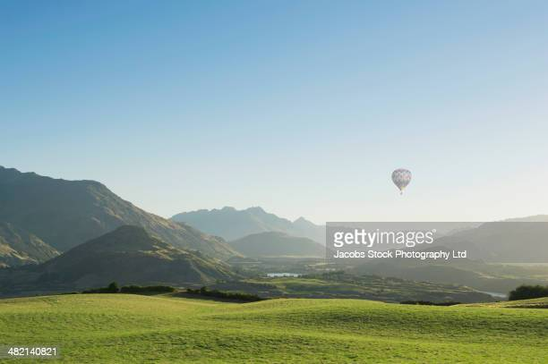 hot air balloon flying above rolling landscape - scenics stock pictures, royalty-free photos & images