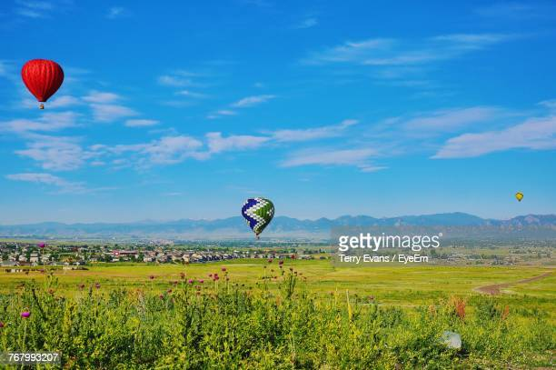 hot air balloon flying over field against sky - fort collins stock pictures, royalty-free photos & images