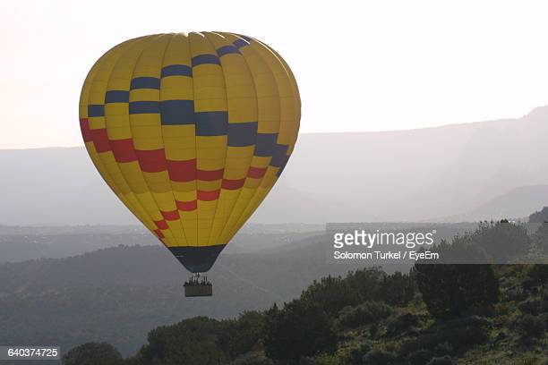 hot air balloon flying over landscape - solomon turkel stock pictures, royalty-free photos & images