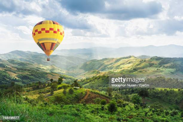 hot air balloon flying over mountains against sky - hot air balloon stock pictures, royalty-free photos & images